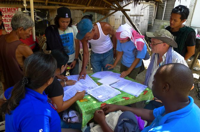 UN-Habitat technical team verifying the location of the houses on the map with community members. Photo by Beryl Jane Dela Cruz.