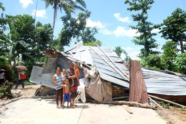 Rogie Alcazaren and family and the remnants of their home—in which they still reside.