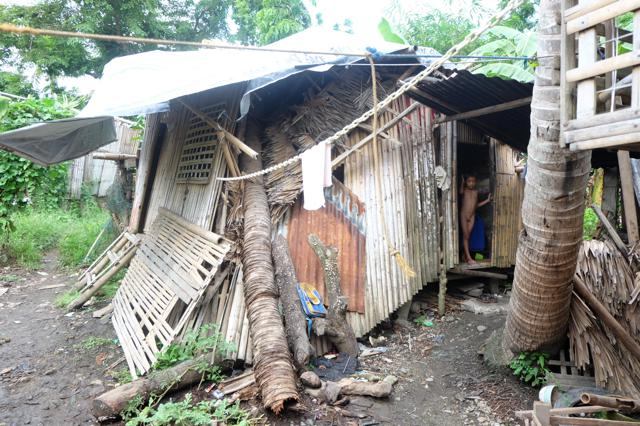 Unable to remove the coconut tree trunk that struck their house during Typhoon Haiyan, a doughnut seller and his son continue to live in perilous conditions and are potential project beneficiaries.